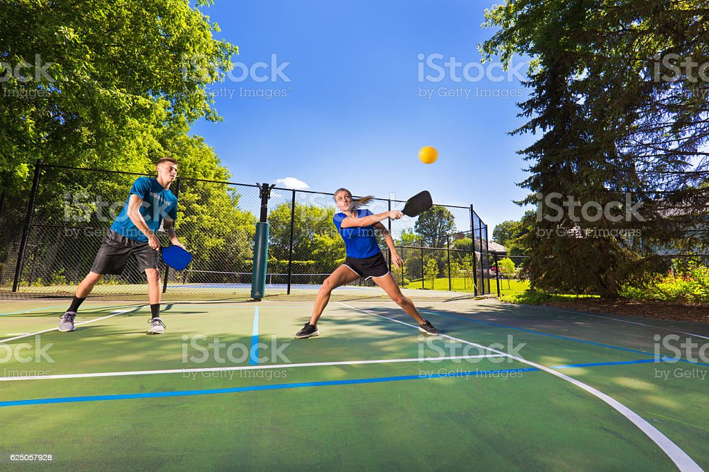 Young Man and Woman Pickleball Player Playing Pickleball in Court stock photo