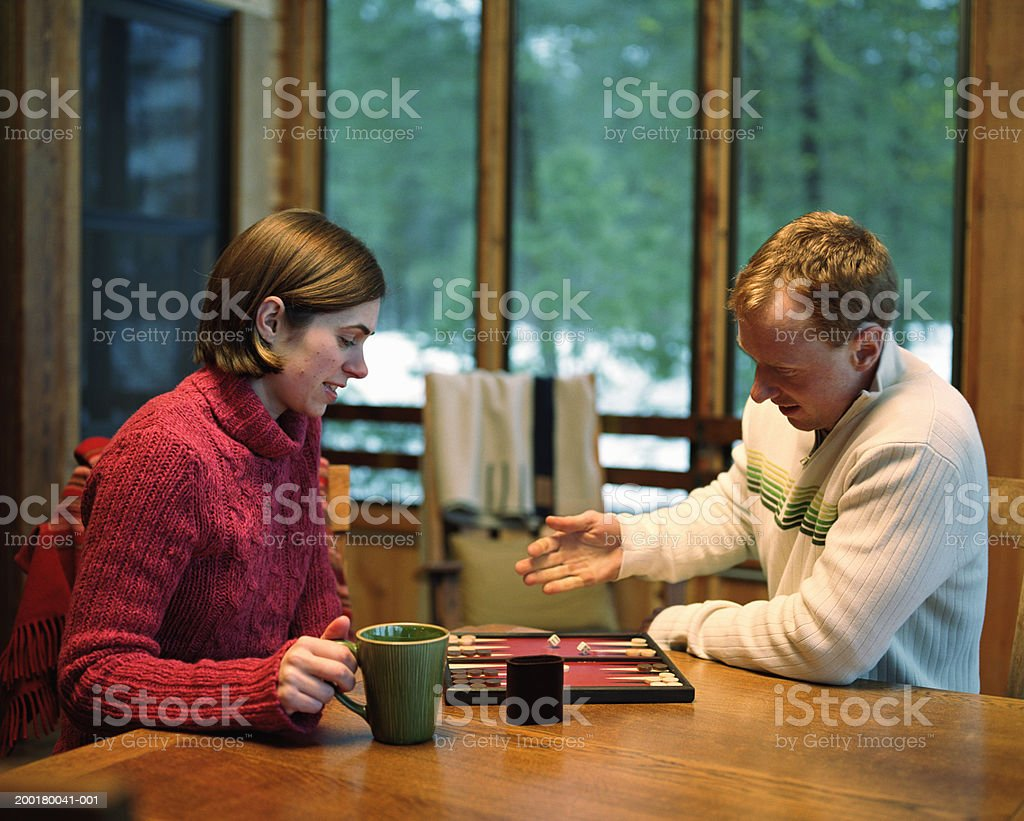 Young man and woman playing backgammon, side view stock photo