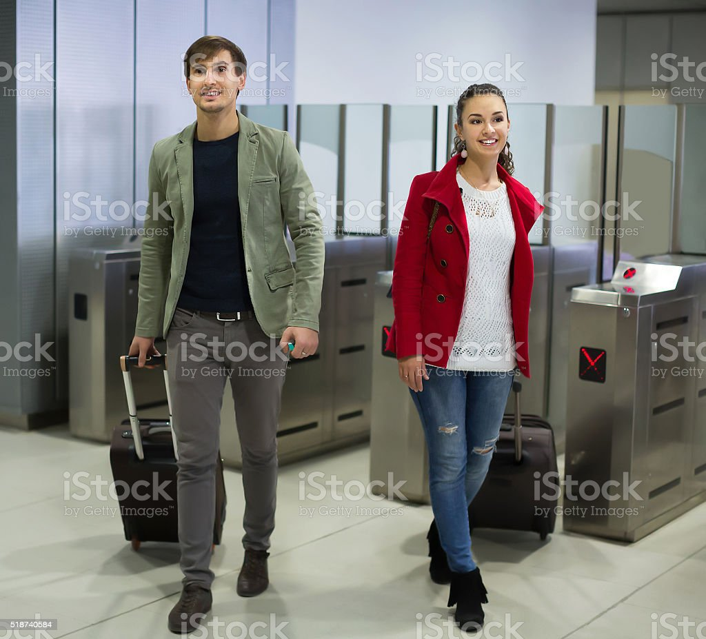 Young man and woman posing at baffle gate stock photo