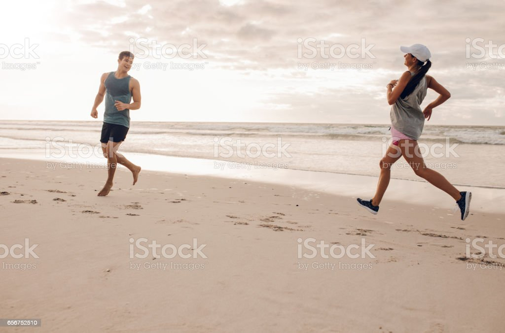Young man and woman running in morning on beach stock photo