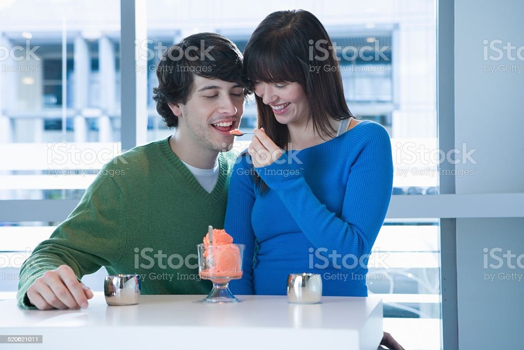 Young man and woman sitting at cafe, woman feeding boyfriend stock photo