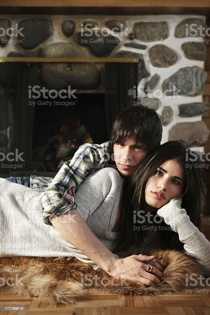 Young man and woman sitting in front of a fireplace royalty-free stock photo