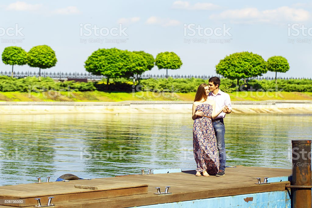 Young man and woman standing together on pier stock photo