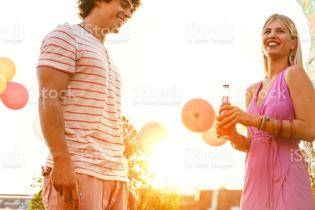 Young man and woman talking on a party stock photo