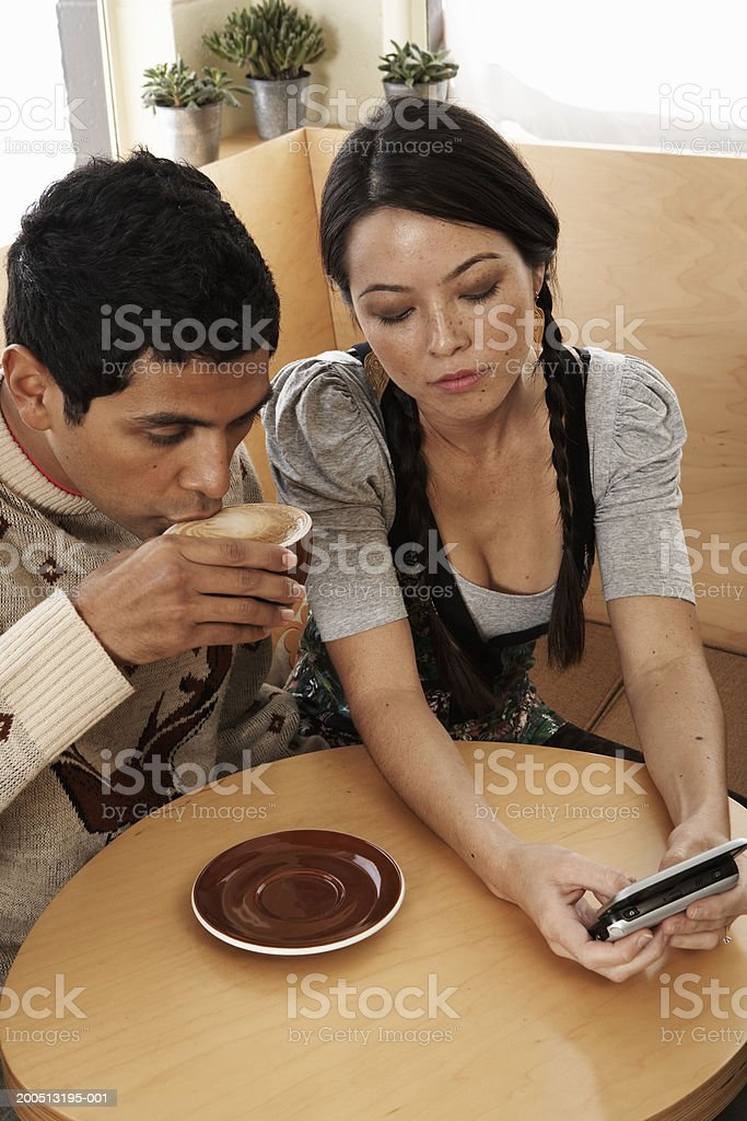 Young man and woman using palmtop in cafe, elevated view stock photo