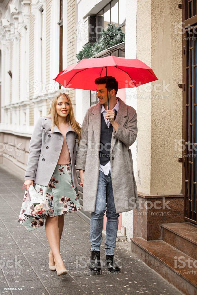 Young man and woman walking on pedestrian on rainy day stock photo
