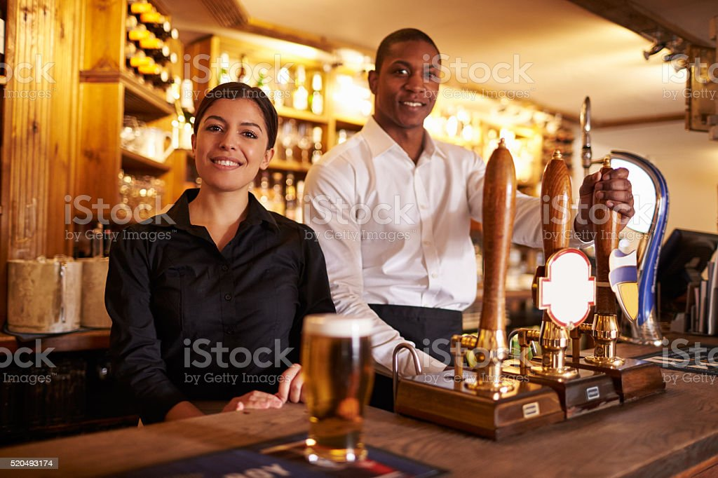 A young man and woman working behind a bar look to stock photo