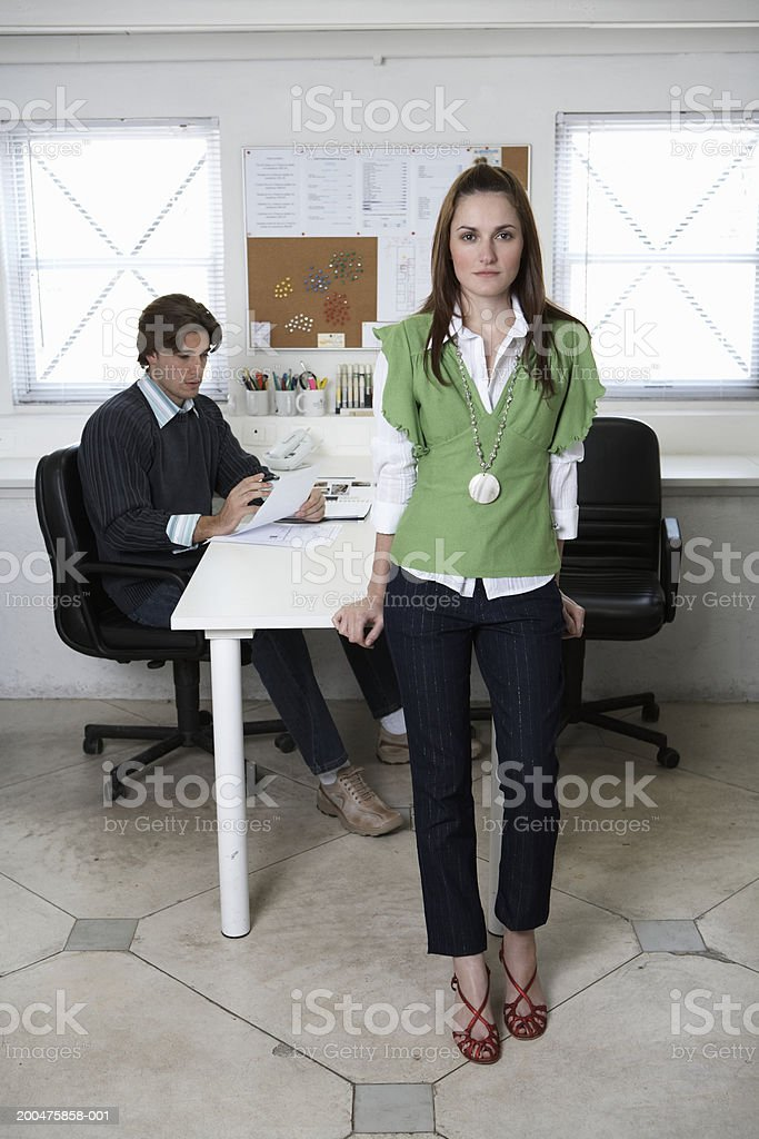 Young man and woman working in office (focus on woman in foreground) stock photo
