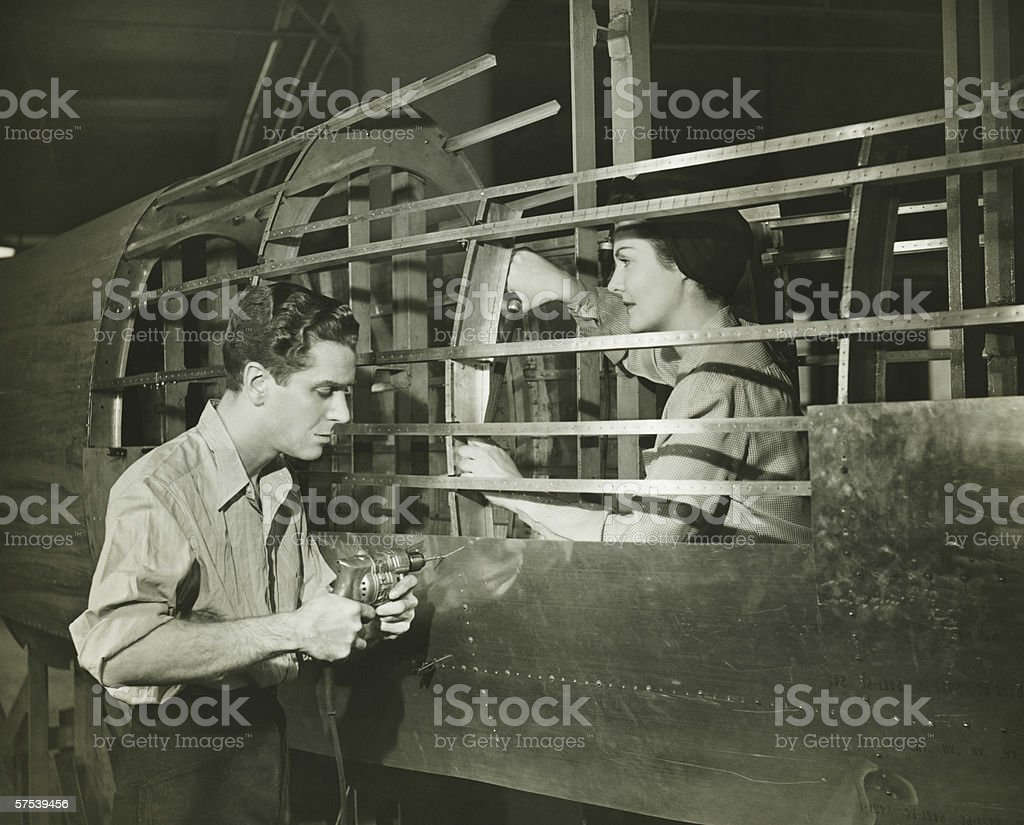 Young man and woman working in plane body in factory, (B&W) royalty-free stock photo