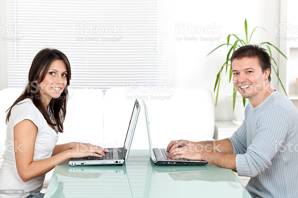 Young man and woman working on laptop computer indoors royalty-free stock photo