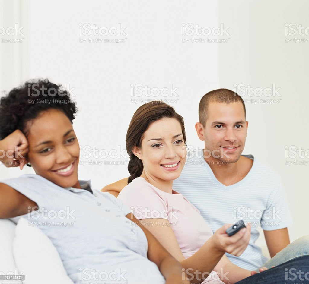 Young man and women sitting together while watching television royalty-free stock photo