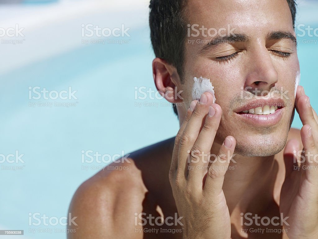 Young man applying lotion to face royalty-free stock photo
