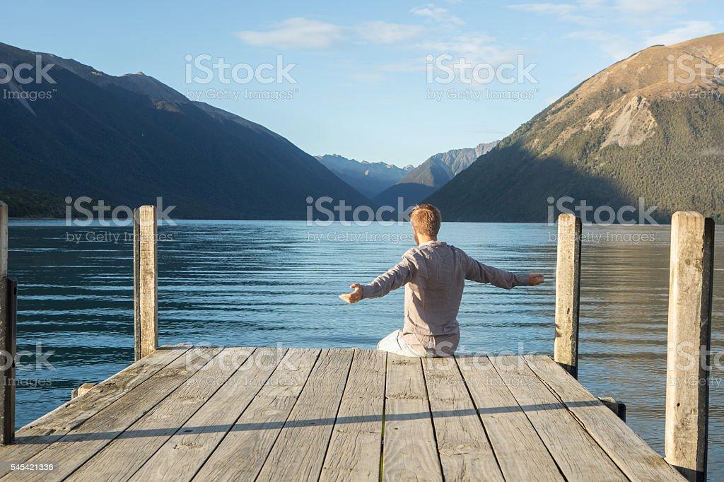 Junger Mann Ausgestreckte Arme auf See Pier in Morgen Sonnenlicht – Foto