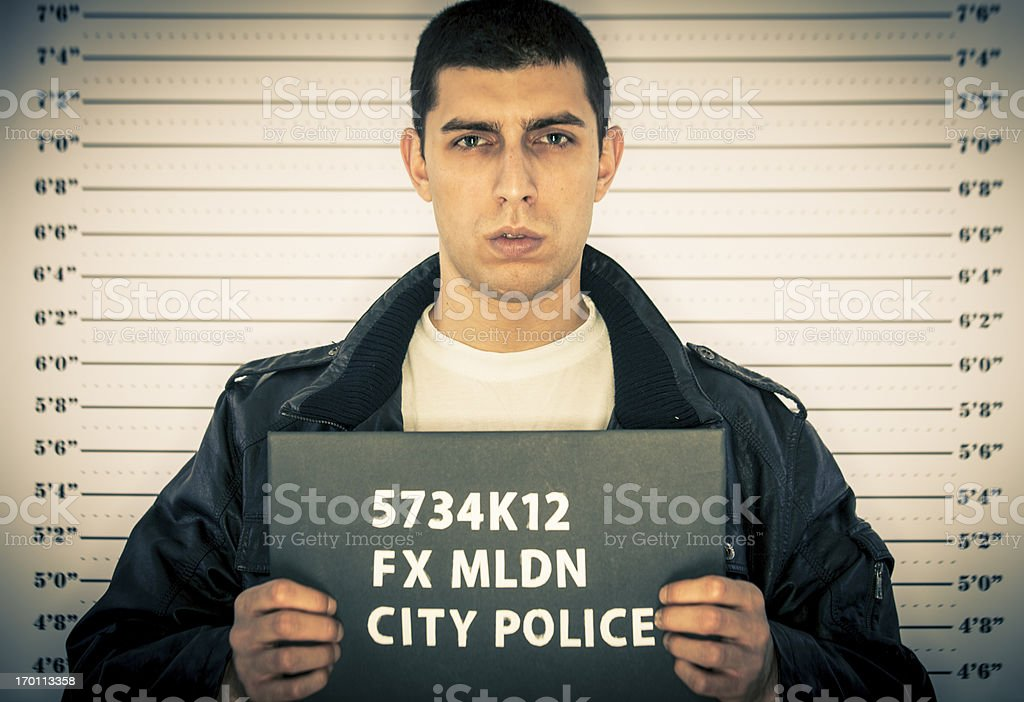 Young man arrested in front of a jail height chart stock photo