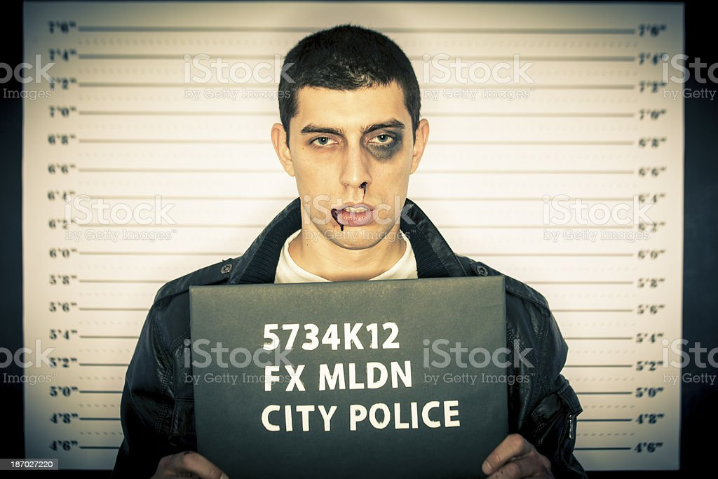 Young man arrested standing in front of a jail chart royalty-free stock photo