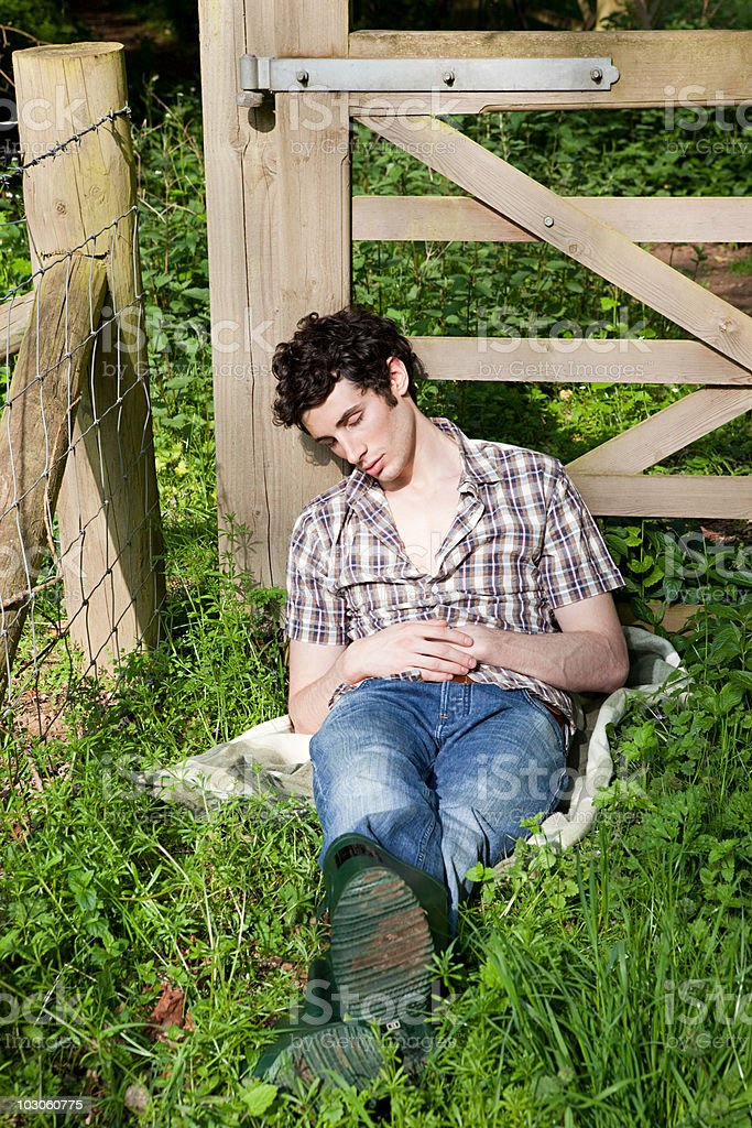 Young man asleep in countryside stock photo