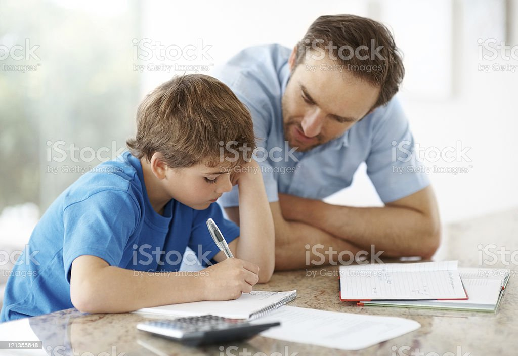 Young man assisting his little son with some home work stock photo
