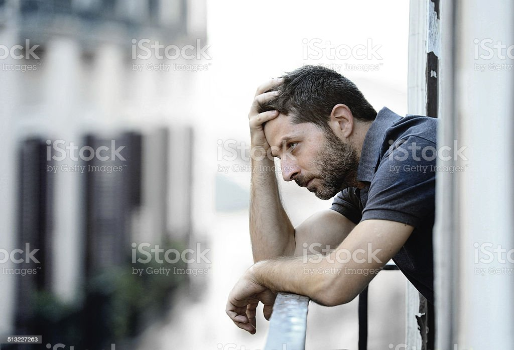 young man at balcony in depression suffering emotional crisis stock photo