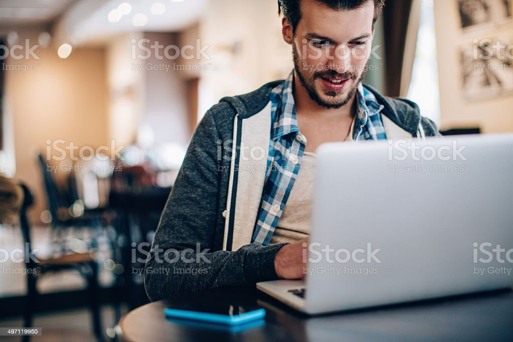 Young man at coffee shop working on a computer stock photo
