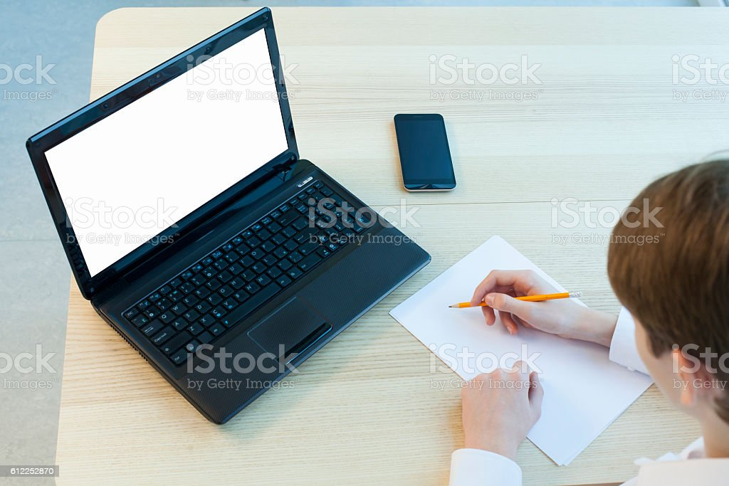 Young man at his desk with a laptop. stock photo