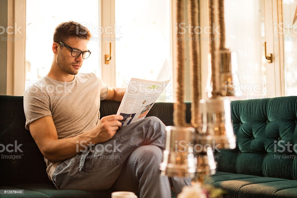Young man at home reading an article in newspapers. stock photo