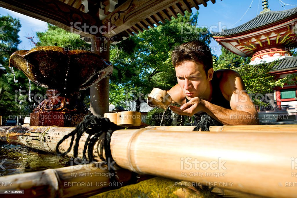 young man at japanese spiritual fountain near Chion-in temple Kyoto stock photo