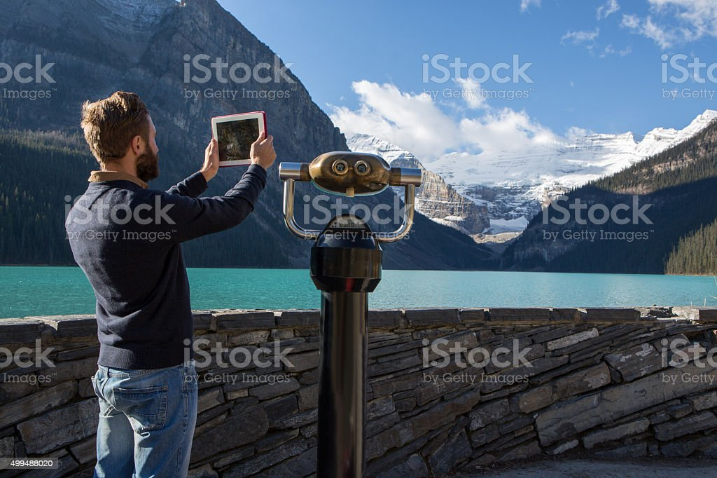 Young man at lake Louise photographing landscape with digital tablet stock photo