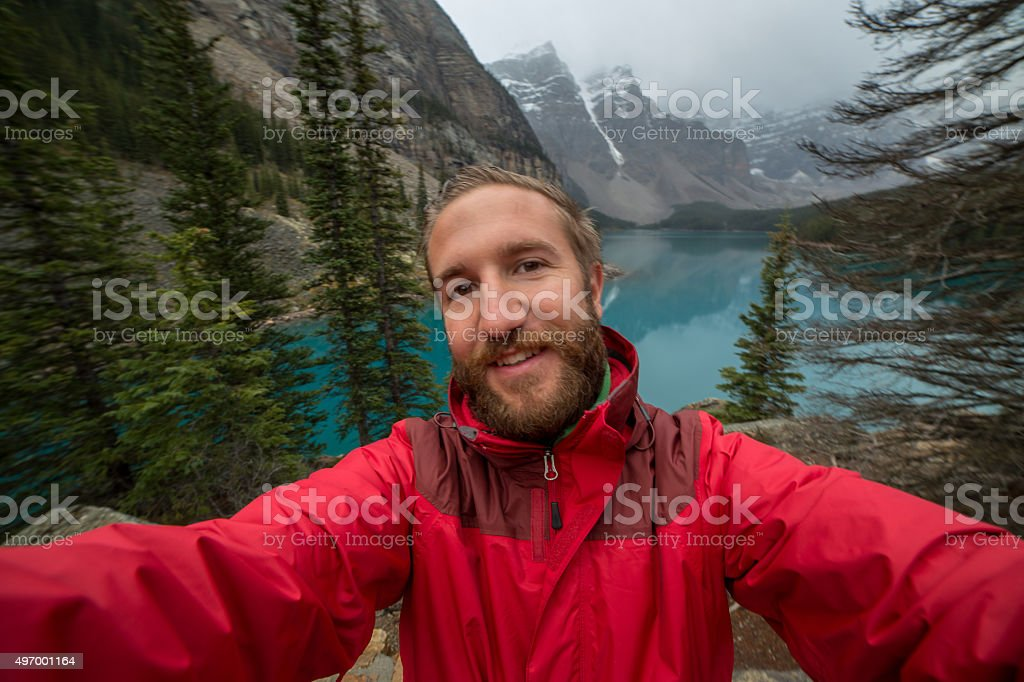 Young man at Moraine lake taking a selfie portrait stock photo