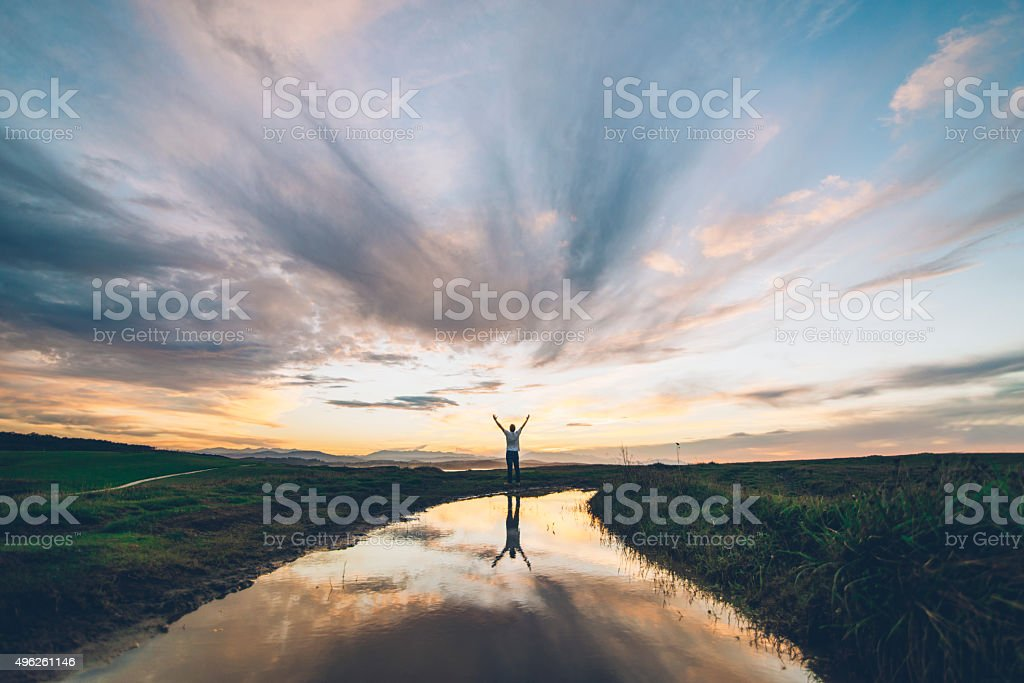 A young man reflected on a puddle at sunset