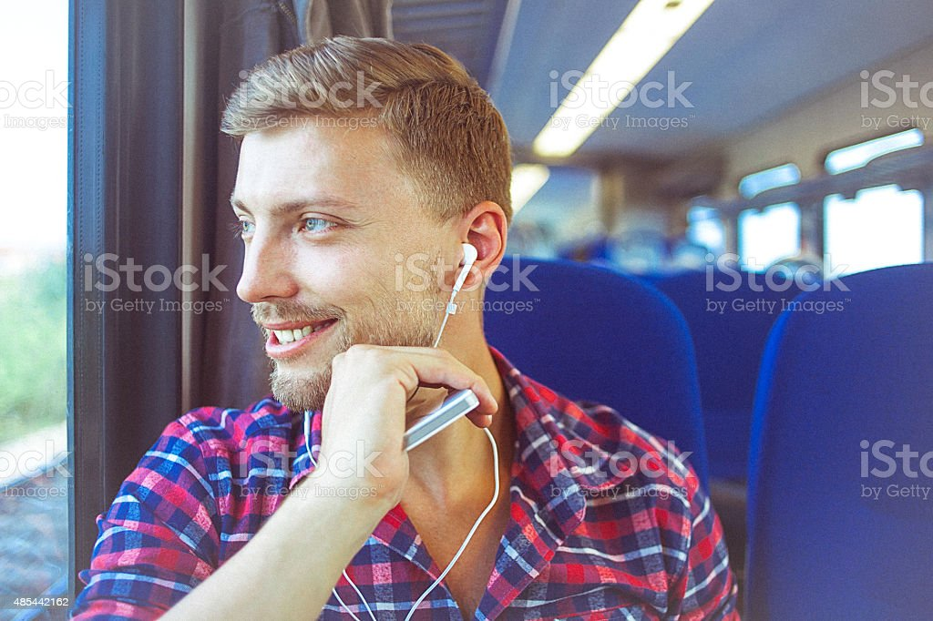 Young man at train using mobile phone and earphones stock photo