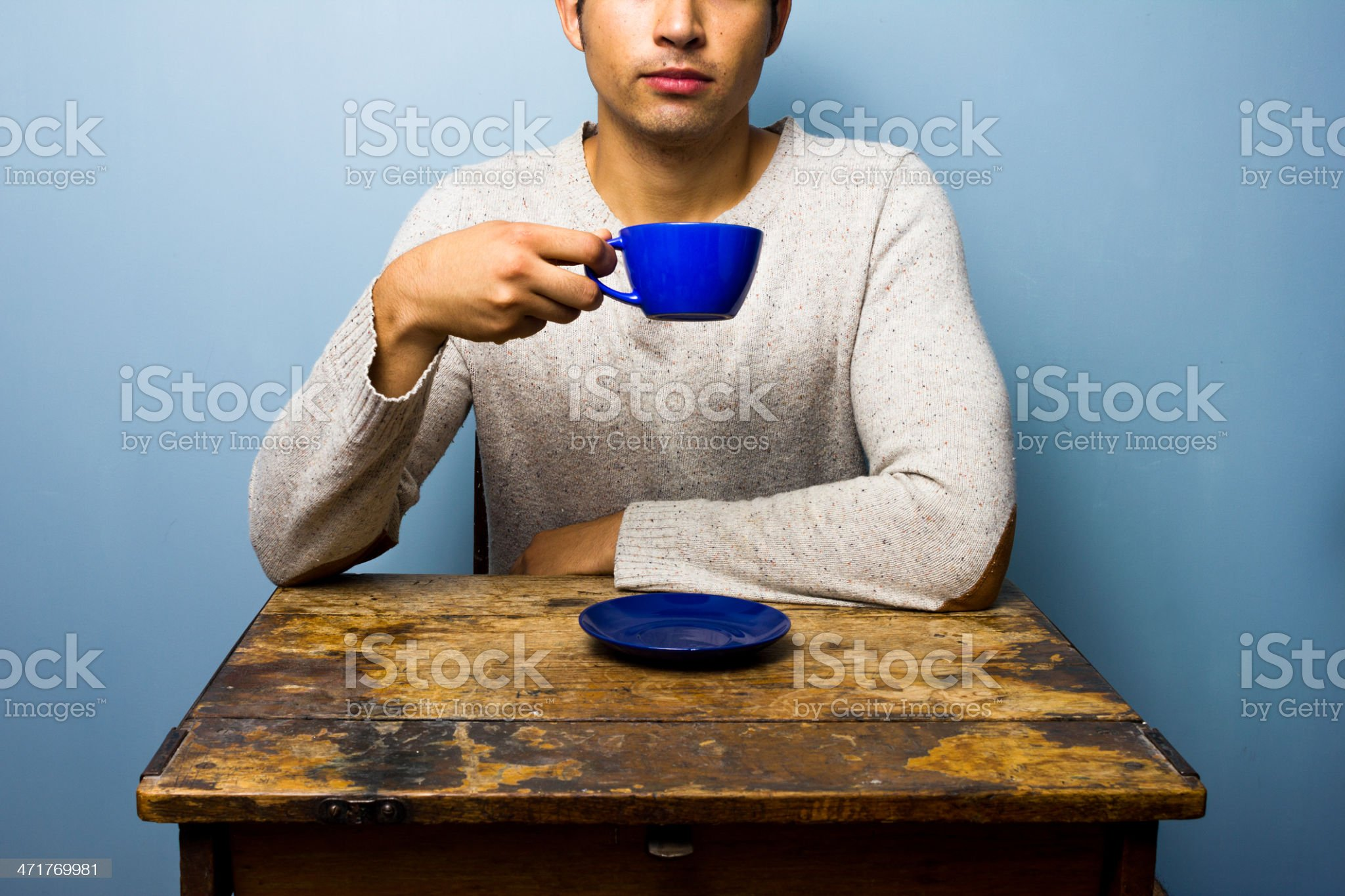 young man at wooden table drinking from cup royalty-free stock photo
