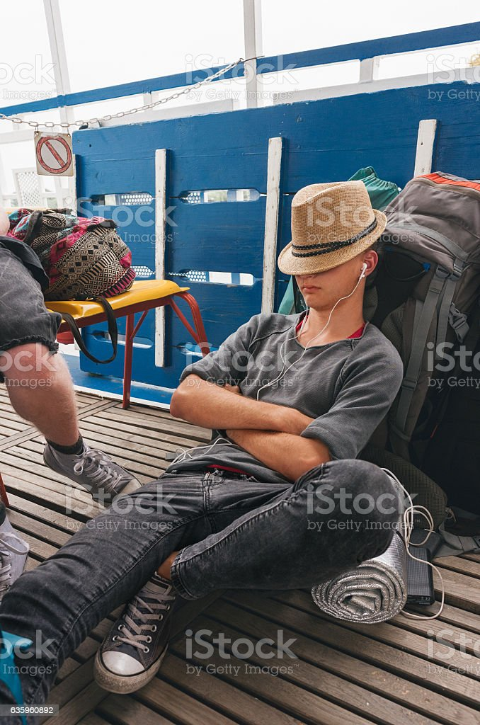 Young man backpacker relaxing on his luggabe stock photo