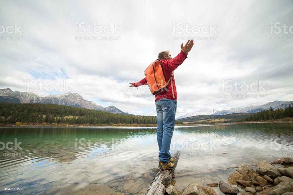 Young man balances on log above lake arms outstretched stock photo