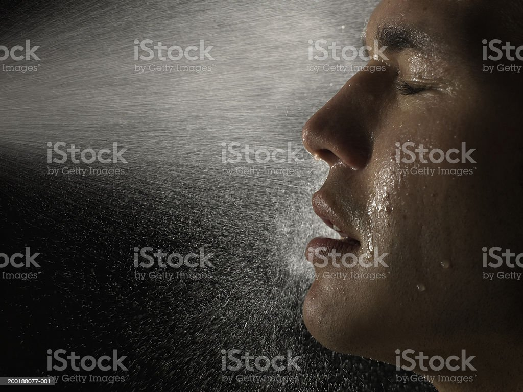 Young man being sprayed in face with water, eyes closed, side view royalty-free stock photo