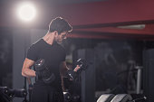 young man biceps curls dumbbells