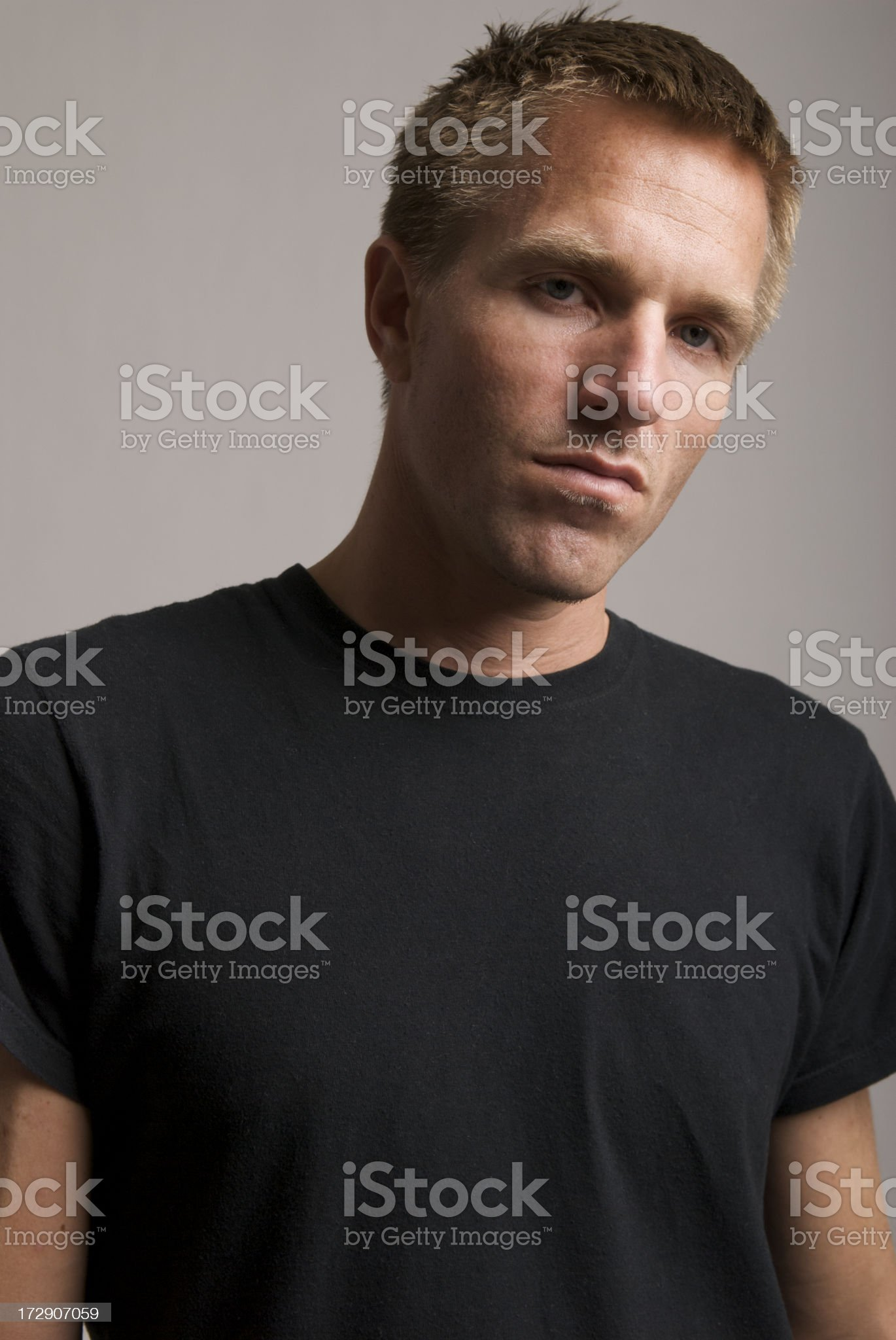 Young Man Blond Hair Black T-Shirt Serious Portrait Indoors royalty-free stock photo