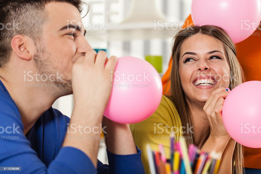 Young man blowing balloon on a party stock photo
