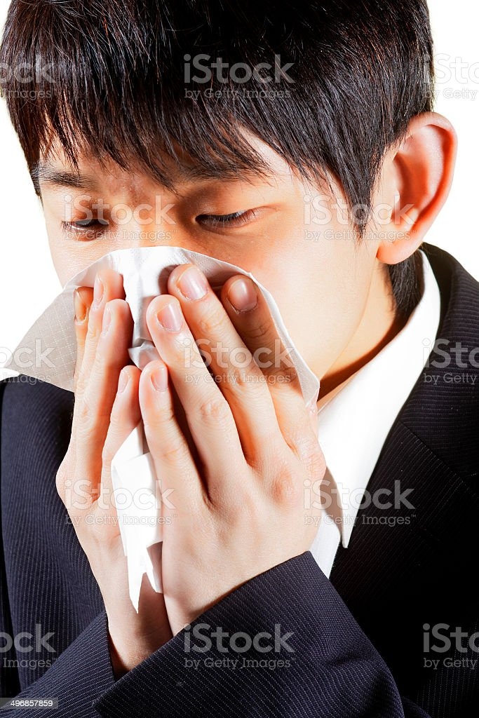 Young Man Blowing Nose into a tissue royalty-free stock photo