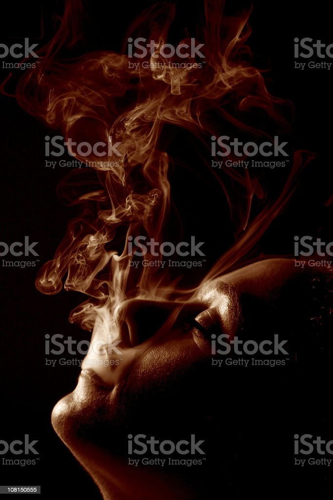Young Man Blowing Smoke Out of Mouth, Toned royalty-free stock photo