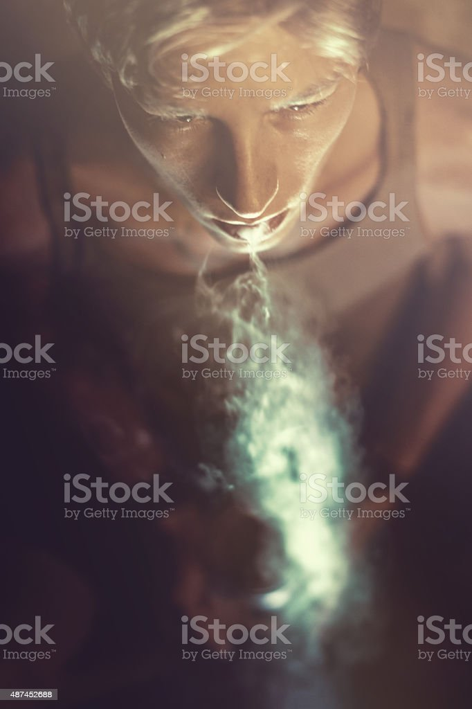Young man blowing smoke stock photo