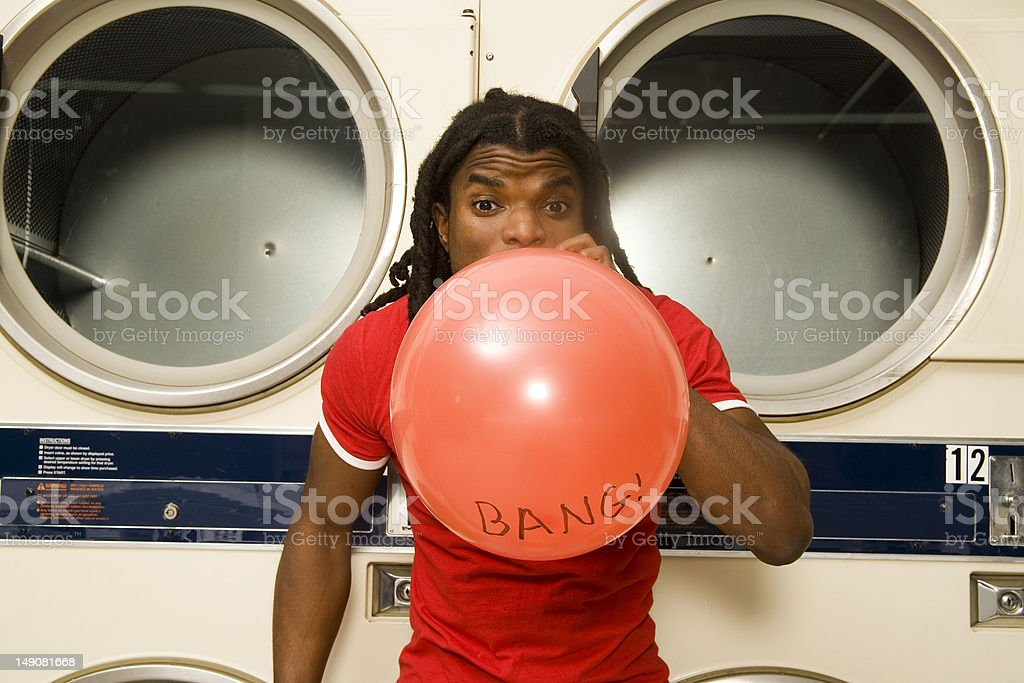 Young man blowing up a balloon at the laundromat. royalty-free stock photo