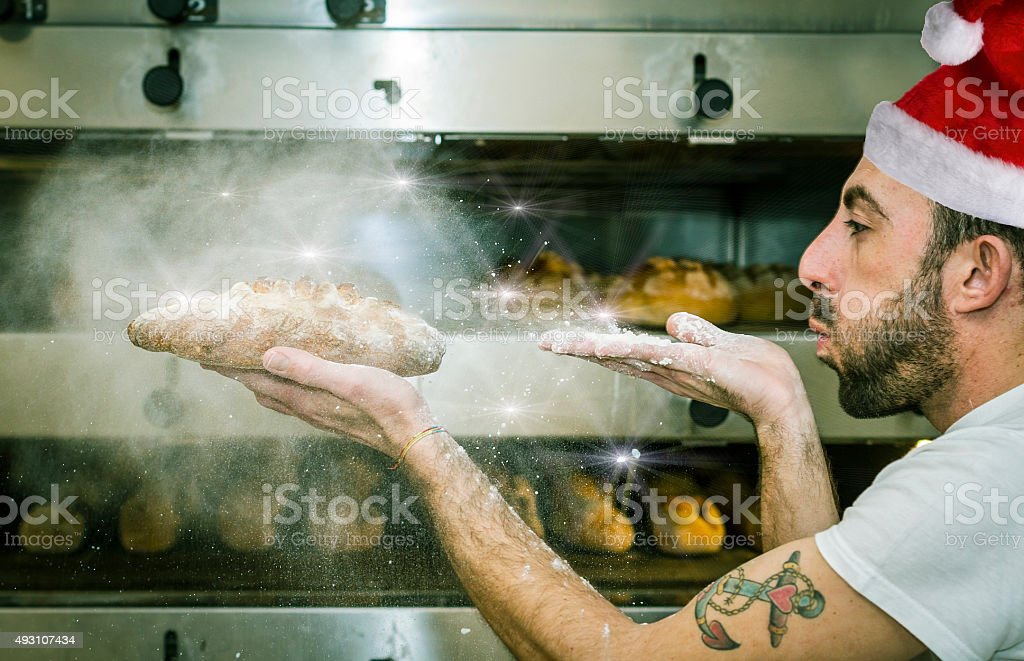 Young man (baker) blows the flour on bread stock photo