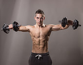 young man bodybuilder looking down, dumbbells exercise.