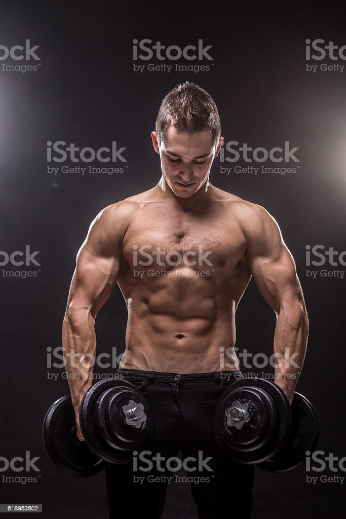 young man bodybuilder looking down holding dumbbells. stock photo