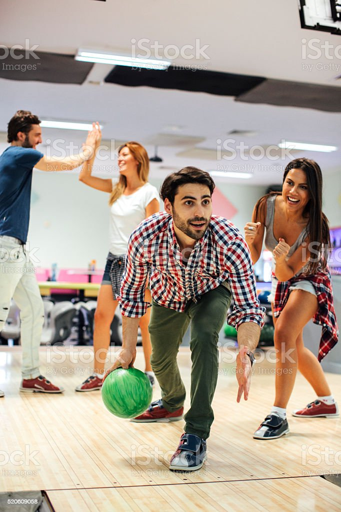 Young Man bowling with his friends. stock photo