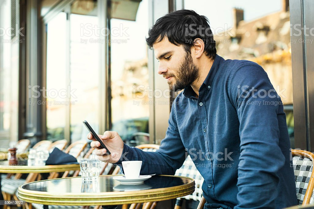 Young Man Browsing Social Media in a Sidewalk Cafe stock photo