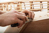 Young man building boat in workshop, close-up of hands