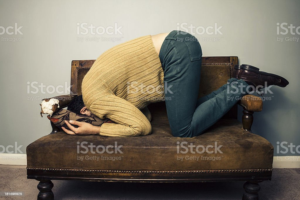 Young man burying his face in old sofa stock photo