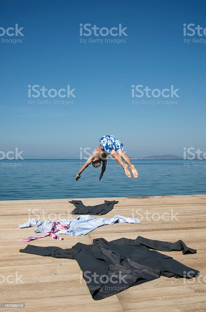 Young Man Businessman Escaping Diving Off Wood Dock stock photo