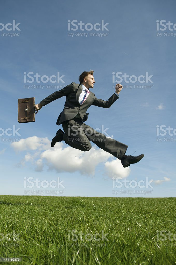 Young Man Businessman Jumping Outdoors Over Green Meadow royalty-free stock photo